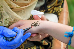 A tattoo artist applying his craft onto the hand of a female. Tool for tattoos tattoo artist make a drawing on the back of the hand of the girl royalty free stock images