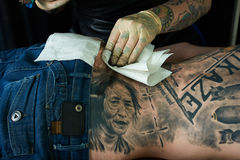 Tattoo artist cleaning skin Royalty Free Stock Photos