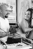 Tattoo artist and customer. Knowing look between tattoo artist and a young female customer while is tattooing her back in the tattoo cabin at his tattoo shop Stock Photo