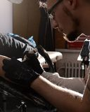 Tattoo artist does the tattoo on his hand man. Closeup.  Royalty Free Stock Photos