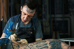 Tattoo artist drawing a tattoo Royalty Free Stock Photography