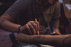 Tattoo artist makes scetch Royalty Free Stock Images