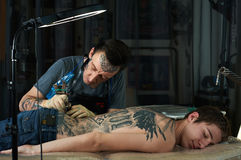 Tattoo artist makes a tattoo on the back Stock Image