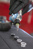 Tattoo artist pouring solvent to small cups with inks Royalty Free Stock Photos