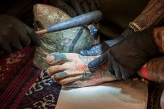 The tattoo artist while practicing a tattoo with the old Samoan. Italy, Florence - 2017, November 3: practicing a tattoo with the traditional Samoan tecnique, at stock photos