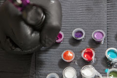 Tattoo artist refilling the pen with pink ink Royalty Free Stock Photos