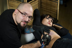 Tattoo artist tattooing happy client. Young tattoo artist tattooing happy client in tattoo shop Stock Photos