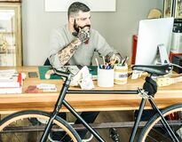 Tattoo artist using computer inside ink studio - Hipster tattoer working on new project - Fashion trends concept - Warm vintage