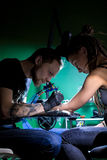 Tattoo artist  which make tattoo. Master works on professional  machine and in sterile  black gloves. Royalty Free Stock Images