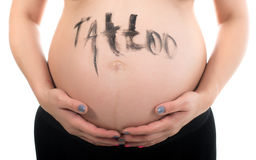 Tattoo artist at work on the pregnant woman body. Stock Photography