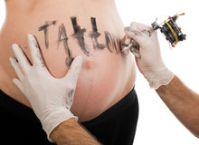 Tattoo artist at work on the pregnant woman body. Stock Photos