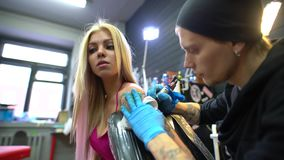 Tattoo artist working with client during workshop stock footage