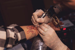 Tattoo artist works in salon Stock Image
