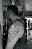Tattoo Artwork. Man with Pacific Island tattoo design on his shoulder waits with other people for his turn in a tattoo studio.(BW royalty free stock photo