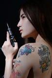 Tattoo asian woman artist holding tattoo machine on dark background stock photo
