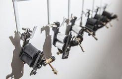 Tattoo coil ink machines hanging from hooks on white wall Stock Image