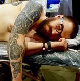 Tattoo Convention, Las Vegas Nevada. Young male receiving tattoo at a convention in Las Vegas Nevada Stock Photo