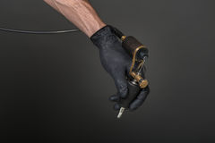Tattoo equipment. Tattoo artist with tattoo equipment in his hand in black glove Royalty Free Stock Photo