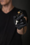 Tattoo equipment. Tattoo artist with tattoo equipment in his hand in black glove Stock Photo