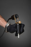Tattoo equipment. Tattoo artist with tattoo equipment in his hand in black glove Stock Image