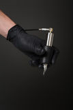 Tattoo equipment. Tattoo artist with tattoo equipment in his hand in black glove Royalty Free Stock Photos