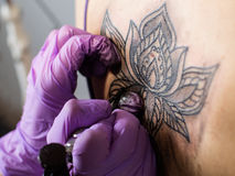 Tattoo flower on the woman's back. Process of making tattoo ( lotus flower) on the woman's back stock images