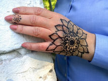 Tattoo in the form of a flower on a woman`s hand. A tattoo made with henna, in the form of a flower on a woman`s hand royalty free stock photos