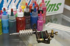 Tattoo Gun with Needles and Ink. A tattoo machine with a package of new needles and bottles of colorful ink, all on a glass table in a studio Stock Images