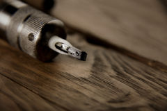 Tattoo gun on a rustic wooden table. Close focus on needles of used contour shiny chrome tattoo gun on a rustic wooden table royalty free stock photo