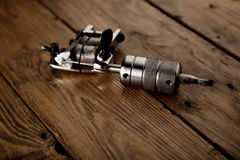 Tattoo gun on a rustic wooden table. Close focus on shiny steel chrome handmade traditional induction tattoo gun on rustic wooden table royalty free stock photos