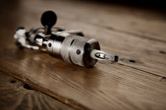 Tattoo gun on a rustic wooden table. Close focus on used contour shiny chrome tattoo gun on a rustic wooden table stock photography