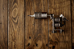 Tattoo gun on a rustic wooden table. Crome steel handmade traditional induction tattoo gun on rustic wooden table top view royalty free stock photography