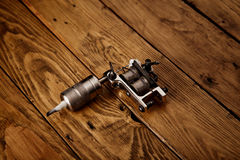 Tattoo gun on a rustic wooden table. Metal handmade classic induction tattoo gun on rough brown table royalty free stock images