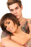 Tattoo Guy With Girl. Tall man with tattos hugging a girl Royalty Free Stock Photography