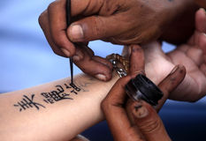 Tattoo Hand. Artist draws a tattoo henna on a female hand. Hieroglyph Beautiful dream royalty free stock photo