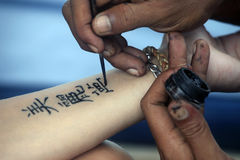 Tattoo Hand. Artist draws a tattoo henna on a female hand. Hieroglyph Beautiful dream stock photography