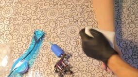 Tattoo machine, hand rub. Tattoo machine lying on the table, rubbing hands stock footage