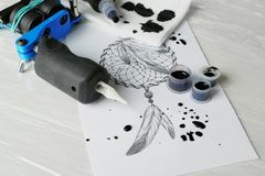 Tattoo machine, sketch and supplies. On table royalty free stock images