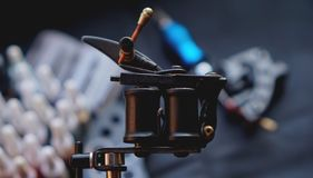 Tattoo machine and tattoo supplies on dark background. For banners stock photos