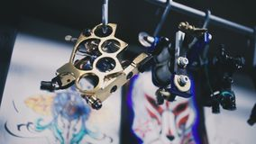 Tattoo machines are hanging on the holder stock video footage