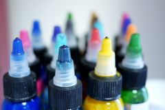 Tattoo maker colors in plastic bottles, shallow de. Tattoo maker colors in plastic bottles stored on shelf, shallow depth of field royalty free stock images
