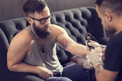 Tattoo. Male tattoo artist holding a tattoo gun, showing a process of making tattoos on a male tattooed model's arm royalty free stock photos