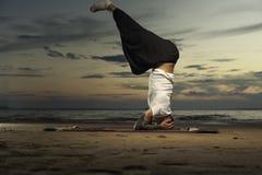 Tattoo man doing high level yoga head stand Stock Photography