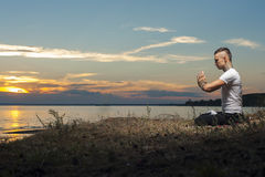 Tattoo man sitting in yoga meditation pose. Young tattoo man sitting on the beach and doing yoga. Meditation Pose royalty free stock image