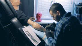 Tattoo master drawing a skull on a bionic hand, robotic prosthesis. 4K stock video footage