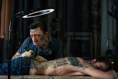 Tattoo master makes faces Stock Photos