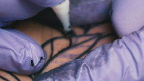 Tattoo master makes the tattoo close-up stock video footage