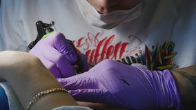 Tattoo master makes the tattoo on a woman`s body close-up stock footage