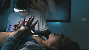 Tattoo master makes the tattoo on a woman`s body stock footage