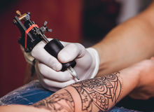 Tattoo master protective gloves make a tattoo in black ink on the hand of the girl. Close-up Royalty Free Stock Photo
